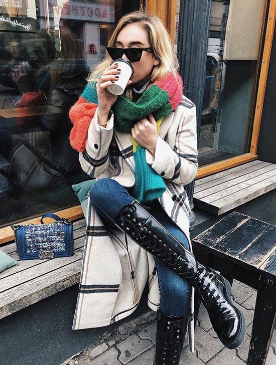 Девушка в армейских ботинках, пальто в клетку и цветном шарфе на шее