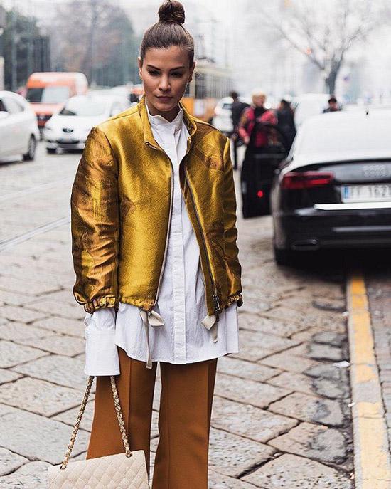 Девушка в белой рубашке, бежевых брюках и золотистой куртке