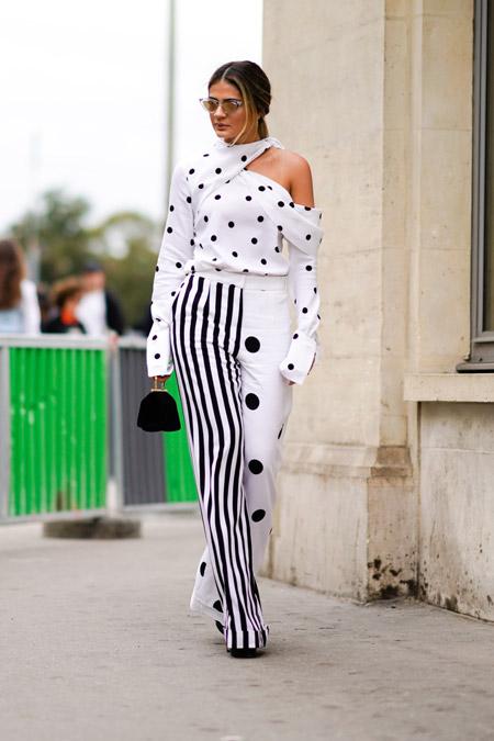 Девушка в белых брюках в полоску и черный горох и ассиметричной блузке в горошек
