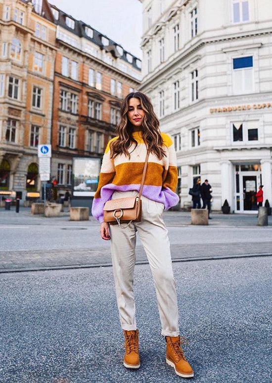 Девушка в брюках, коричневых ботинках и цветном джемпере