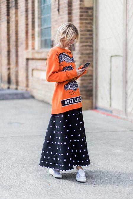 Девушка в черной длинной юбке в белый горох и оранжевый свитшот с принтом
