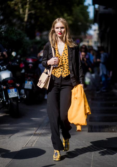 Девушка в черных брюках и оранжевой жилетке в горошек