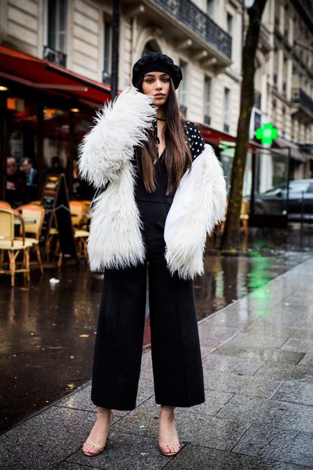 Девушка в черных широких брюках, черная блузка в белый горошек и белый полушубок