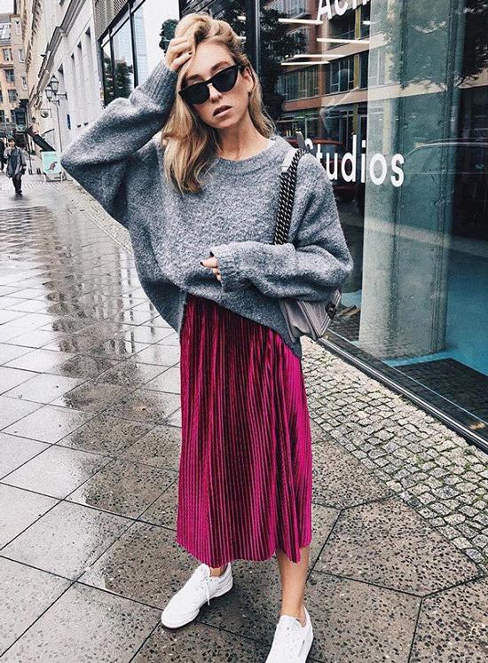 Девушка в фиолетовой плиссированной юбке и сером джемпере