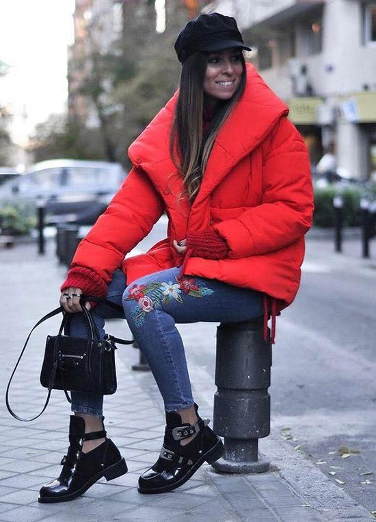 Девушка в красно пуховике, черной кепи и джинсах с росшивкой