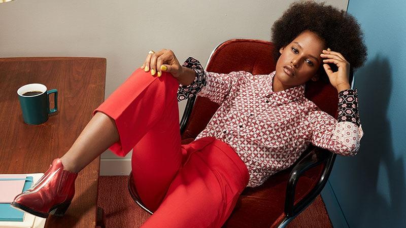 Девушка в красных брюкх и блузке с принтом