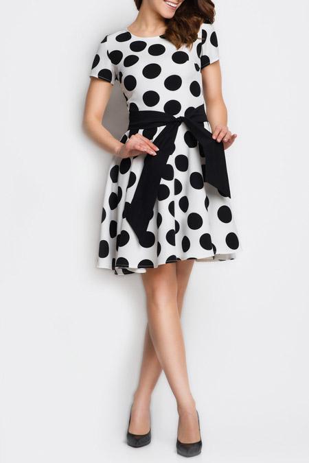 Девушка в легком платье в черный горошек с поясом