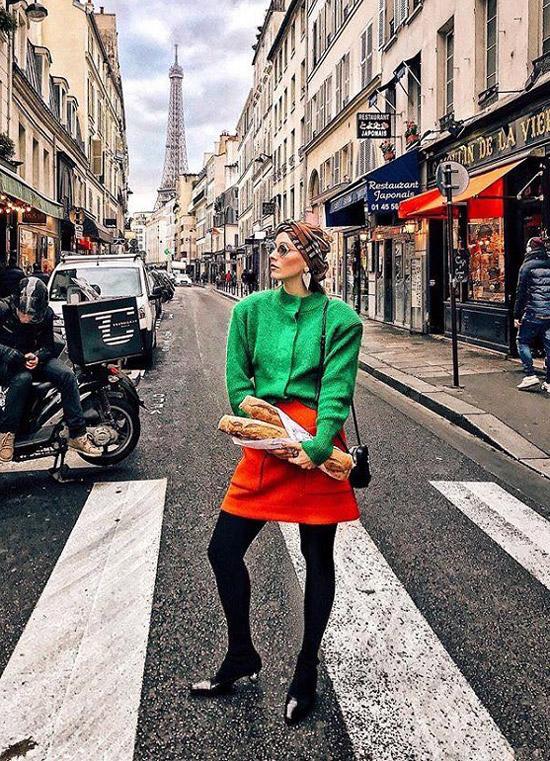 Девушка в оранжевой юбке, зеленой кофте и черных туфлях