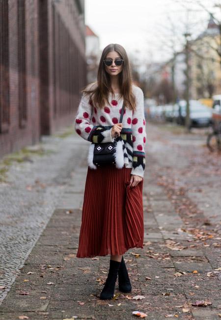 Девушка в плиссированной юбке миди и белый свитер в красный горох, черные ботильоны