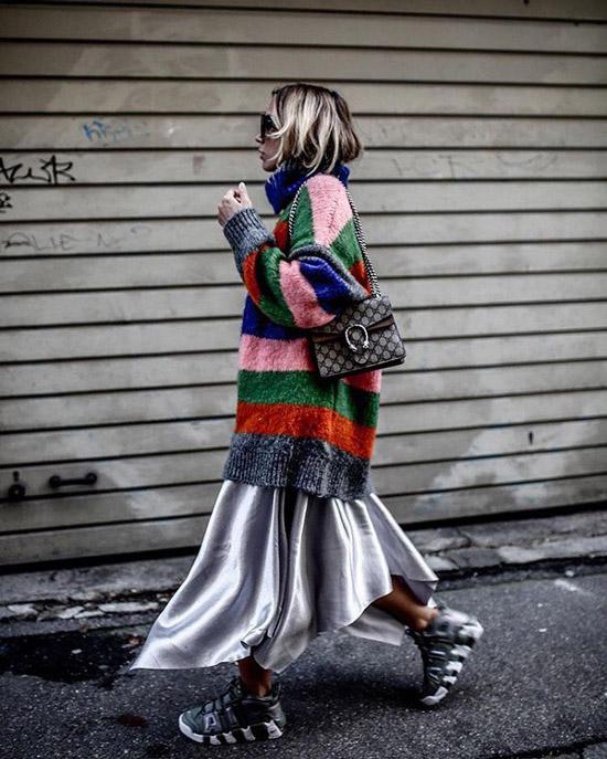 Девушка в сером платье, кросовках и цветном полосатом свитере