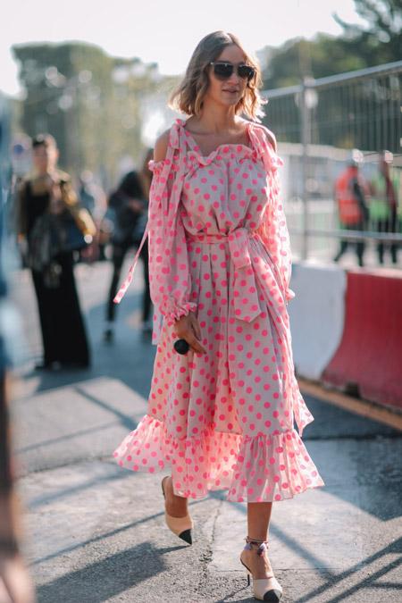 Девушка в светлом платье с воланами в розовый горошеу, бежевые босоножки с острым черным носом