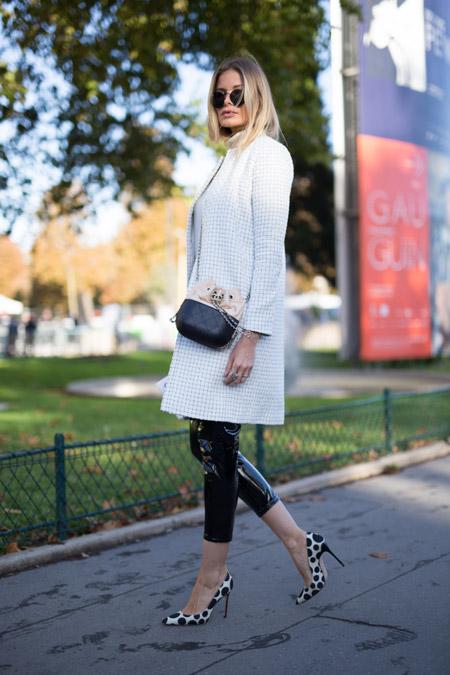 Девушка в светлом тренче и кожаных лосинах, туфли на шпильке в черный горошек