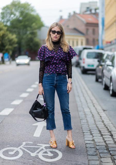 Девушка в укороченных джинсах, черная блузка с волнами в фиолетовый горох и золотые босоножки