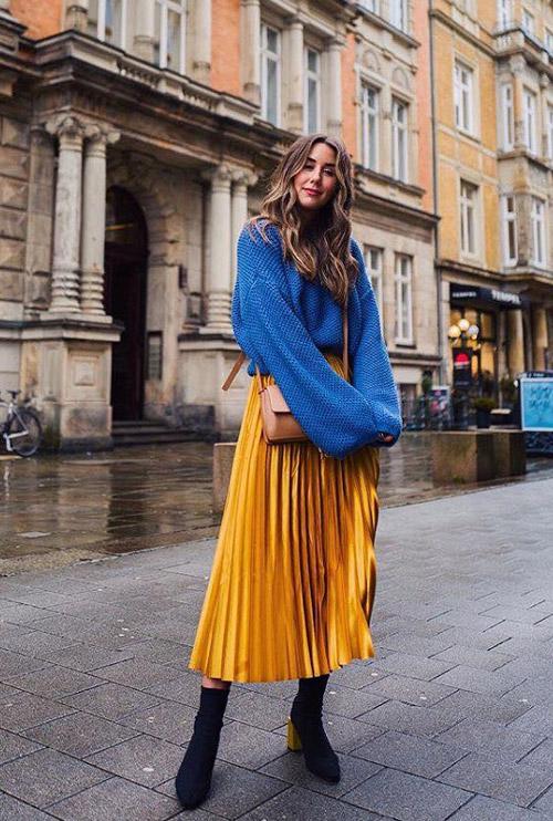 Девушка в золотой юбке плиссе и синем джемпере