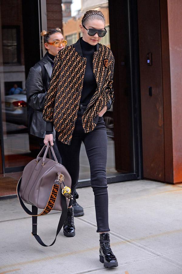 Джиджи Хадид в черной водолазке и джинсах, куртка бомбер с принтом, лакированые ботинки и объемная сумка