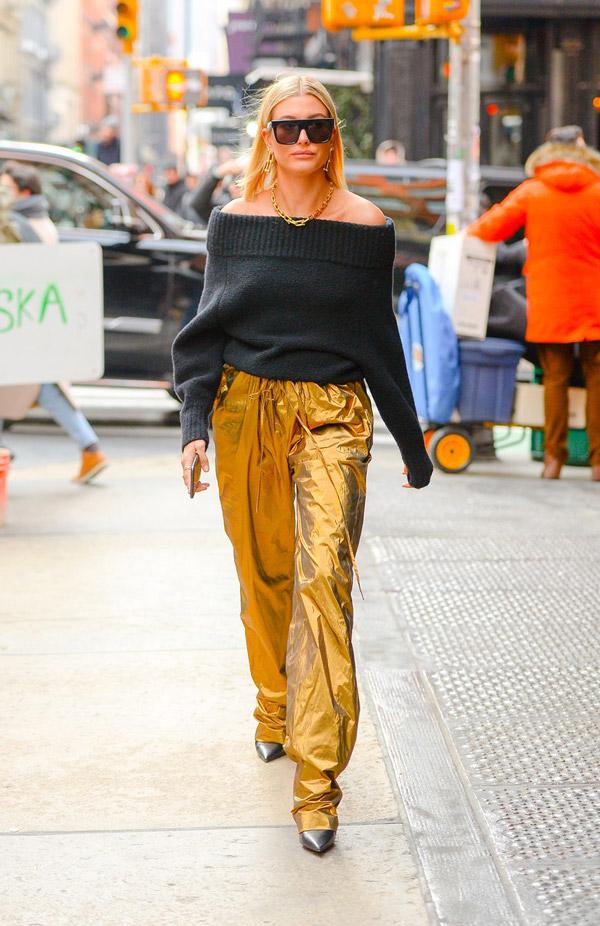 Хейли Болдуин в золотых широких брюках и черном свитере