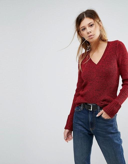 Модель в джинсах и бордовом свитере