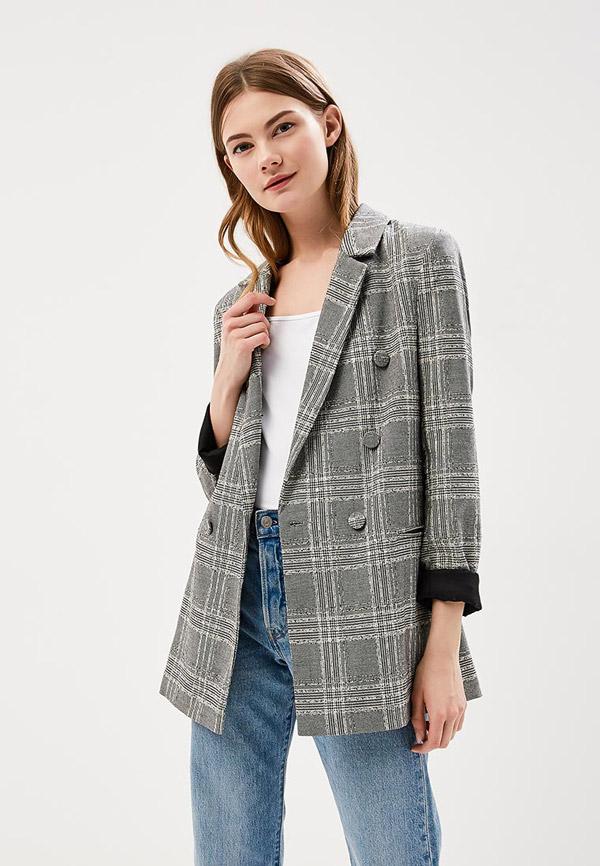 Модель в джинсах сером пиджаке в клетку