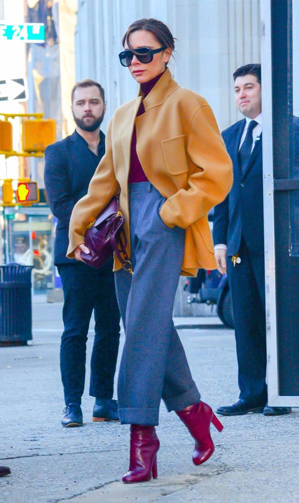 Виктория Бекхэм в широких брюках, пиджак горчичного цвета, бордовая водолазка, споги и сумка