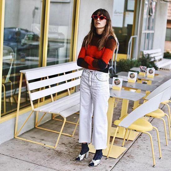 Девушк в белых джинсах, свитер, носки и босоножки на каблуке