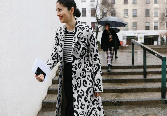 Девушка в белом пальто с черными узорами, тельняшка и черная юбка