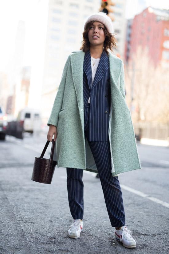 Девушка в брючном костюме в полоску и мятном пальто
