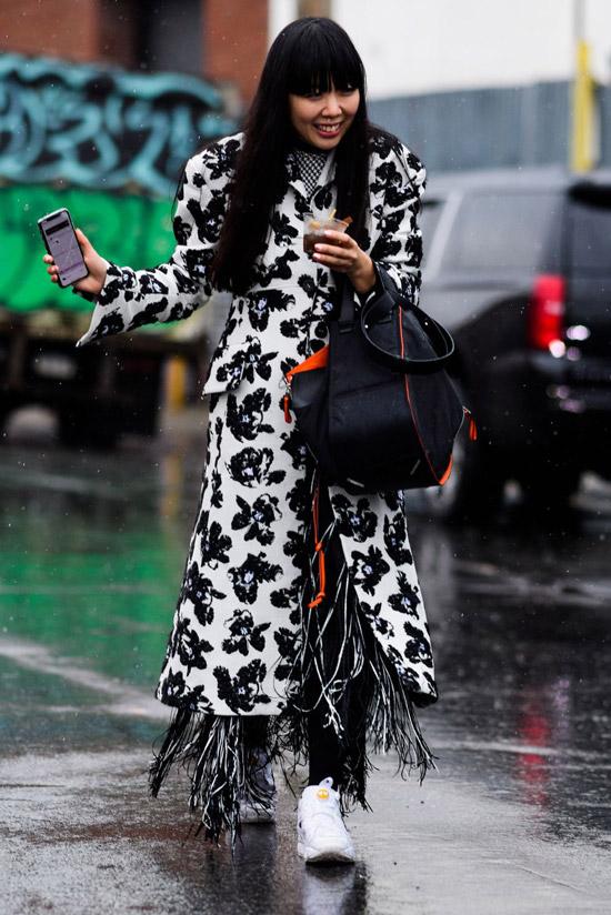 Девушка в длинном белом пальто с черным принтом, белые кроссовки