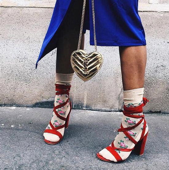 Девушка в красных босоножках и бежевых носкх с цветами