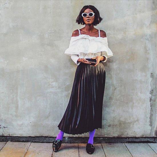 Девушка в плиссированой юбке, белый топ и фиолетовые носки