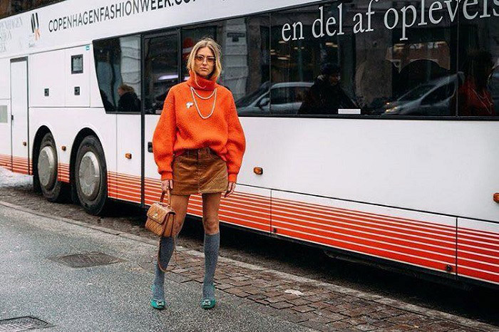 Девушка в серых гольфах, мини юбка и оранжевый свитер