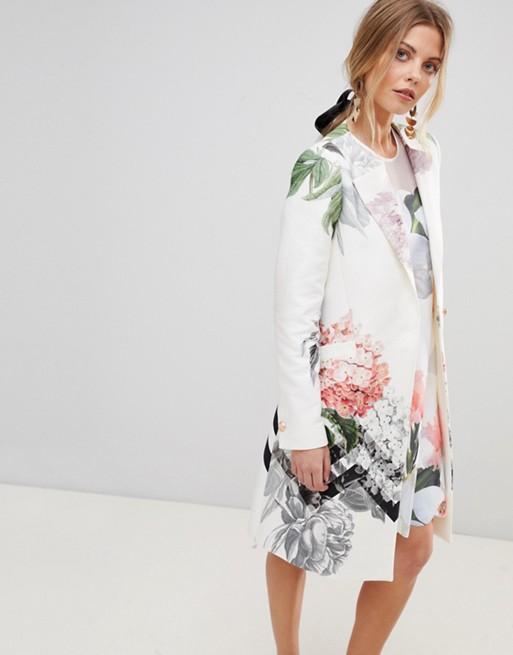Модель в белом пльто с цветочным принтом
