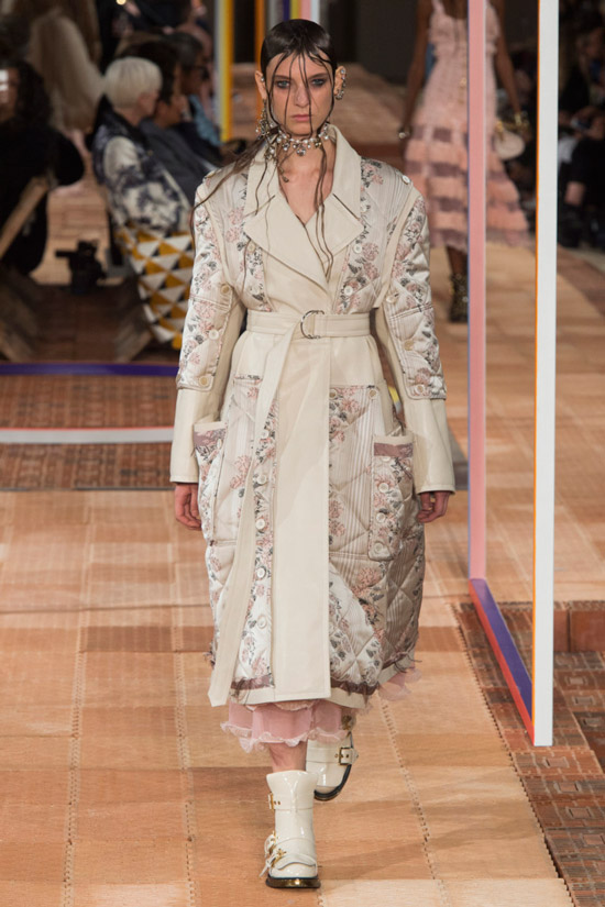 Модель в бежевом пальто с поясом и цветочным принтом от Alexander McQueen