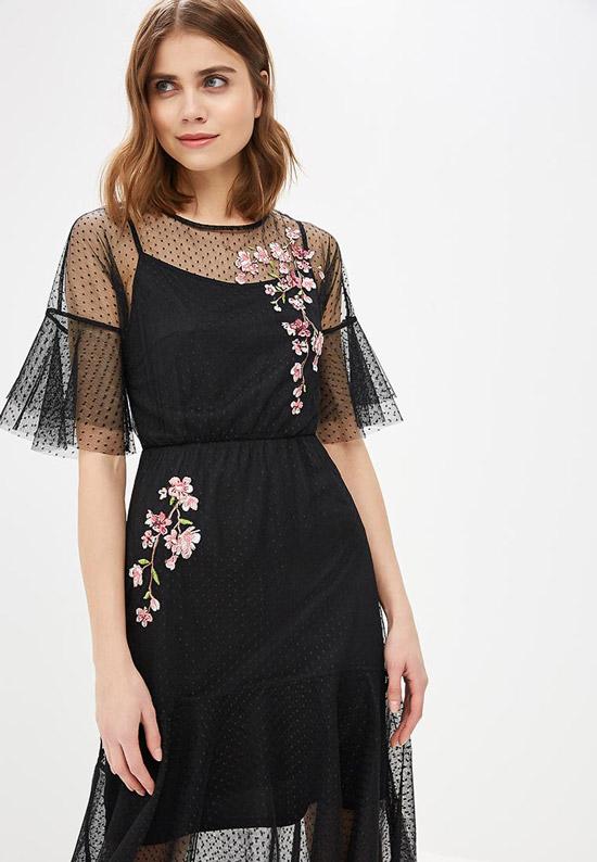 Модель в черном платье с прозрачными рукавами и вышивкой