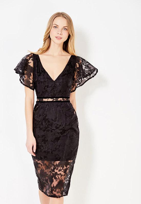 Модель в черной кружевном платье с глубоким декольте и золотым поясом