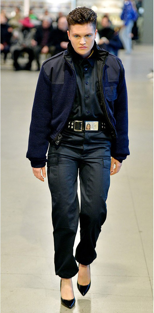 Модель в черных брюках и темном бомбере от Vetements