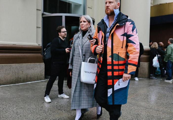 Женщина в двубортном сером пальто в клетку