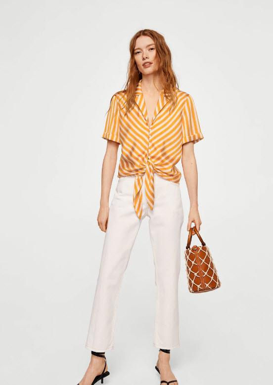 Девушка в желтой блузке в полоску с v образным вырезом и белые брюки