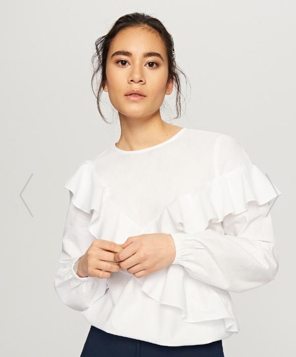 Модель с белой блузке без воротника с рюшами