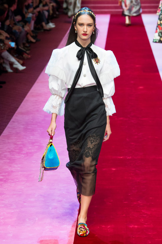 Модель в белой блузке с пышнами рукавами и черным бантом, черная узкая юбка от Dolce & Gabbana