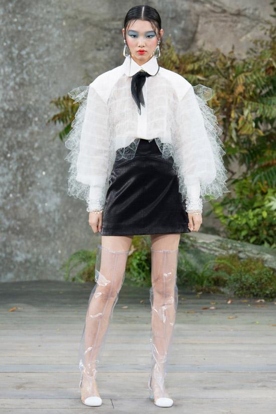 Модель в белой блузке с пышными руквами, черной мини юбке и прозрачные сапоги от Chanel
