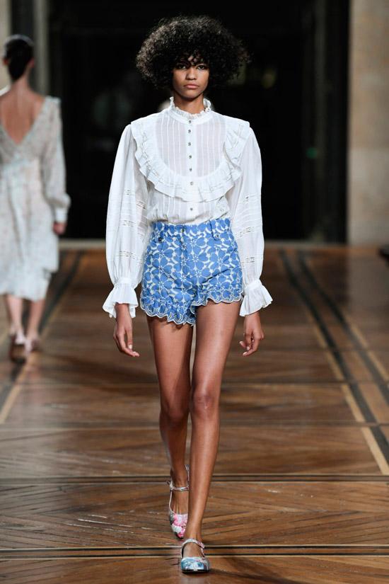 Модель в белой блузке с рюшами и голубые шорты от Paul & Joe