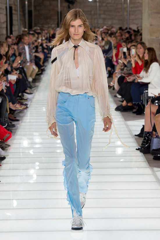 Модель в бежевой прозрачной блузке и голубые брюки от Louis Vuitton