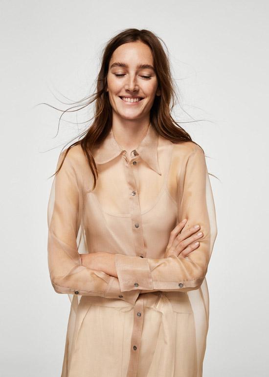 Модель в бежевой прозрачной блузке