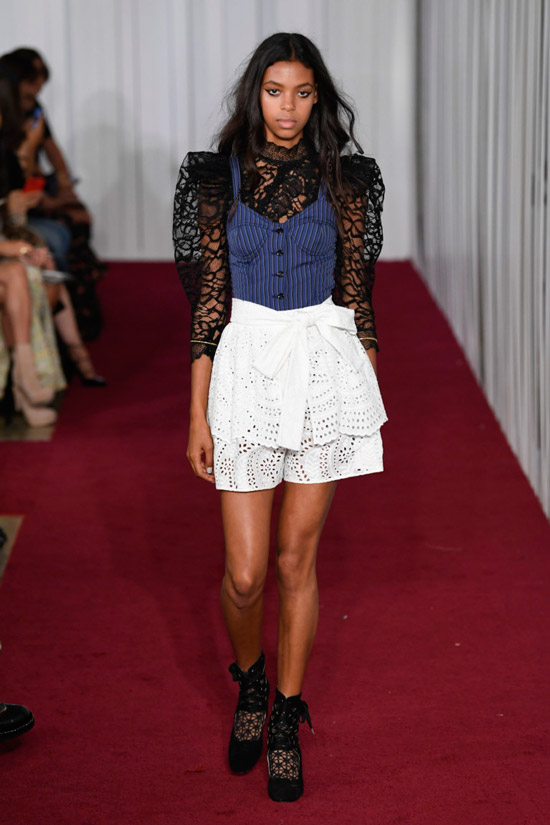 Модель в черной блузке с синим корсетом и белая юбка от Jill Stuart