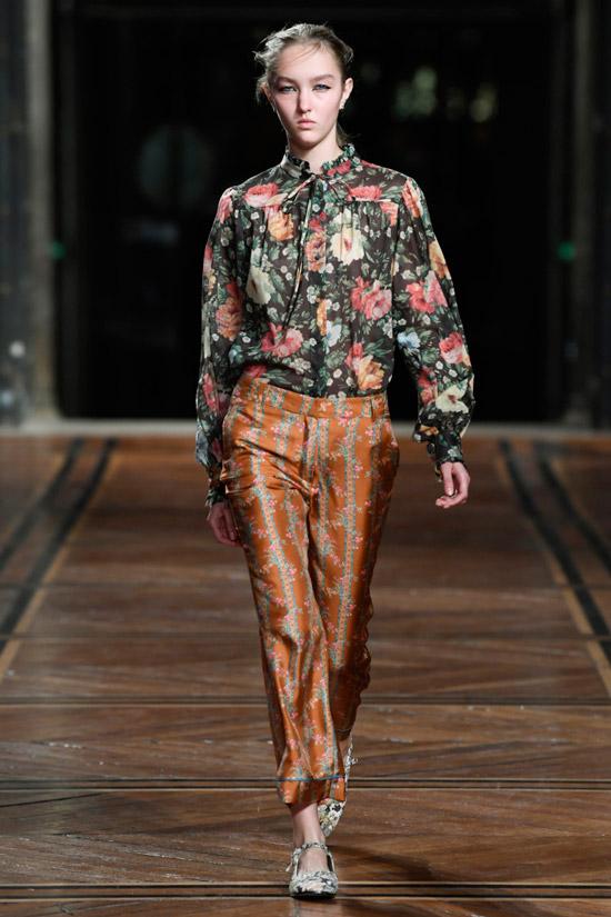 Модель в черной блузке с цветочным принтом и брюках от Paul & Joe