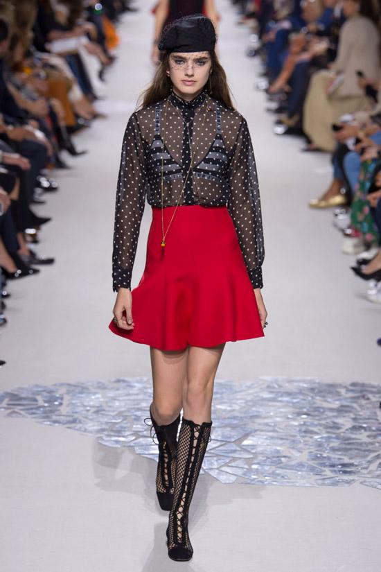 Модель в черной прозрачной блузке и красной мини юбке от Christian Dior