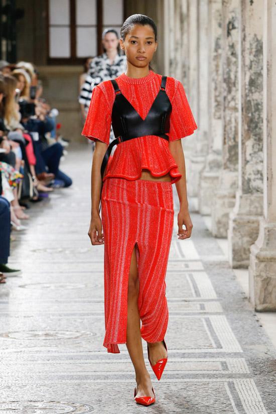 Модель в красной блузке с черным корсетом и красная юбка миди с разрезом от Proenza Schouler