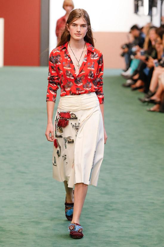 Модель в красной блузке с принтом и светлой юбке миди от Charm's