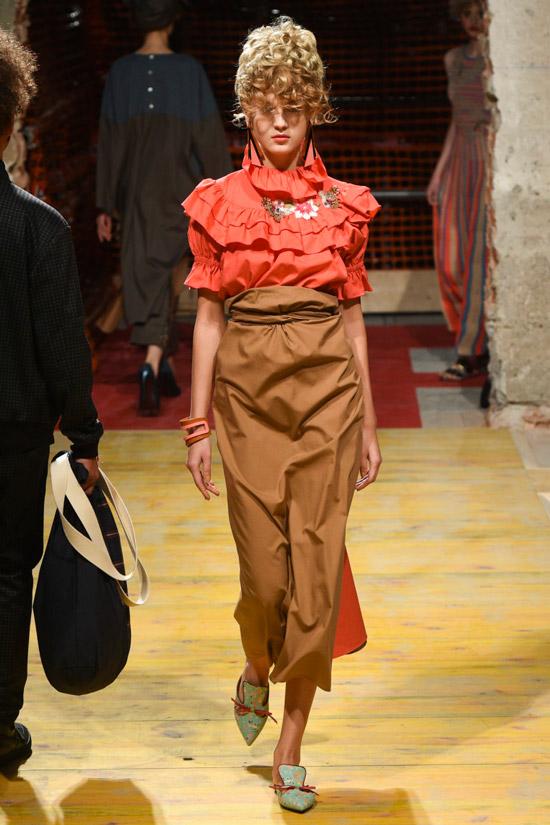 Модель в красной блузке с рюшами и юбке миди песочного цвета от Antonio Marras