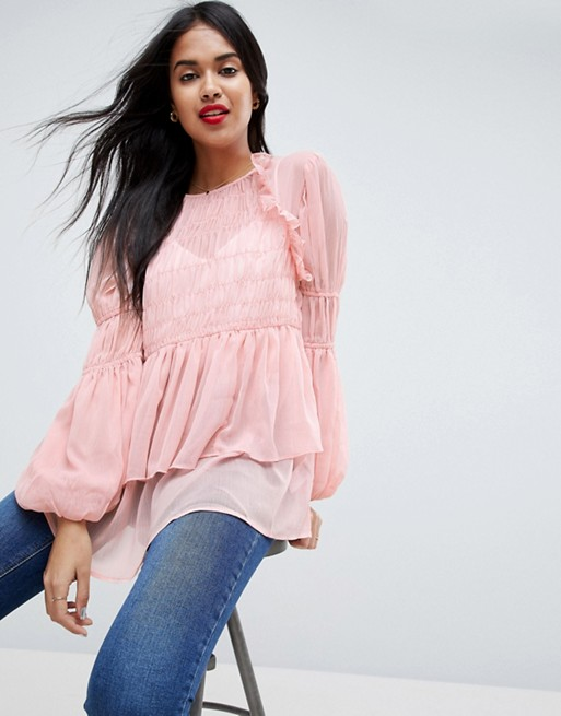 Модель в легкой розовой блузке с пышными рукавами